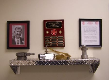 A Dan Newton display including a black and white photo of him, a plaque, and a letter. Below those i