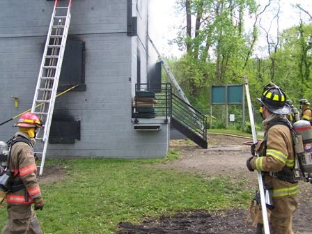 Two firefighters standing in front of a training facility holding poles.