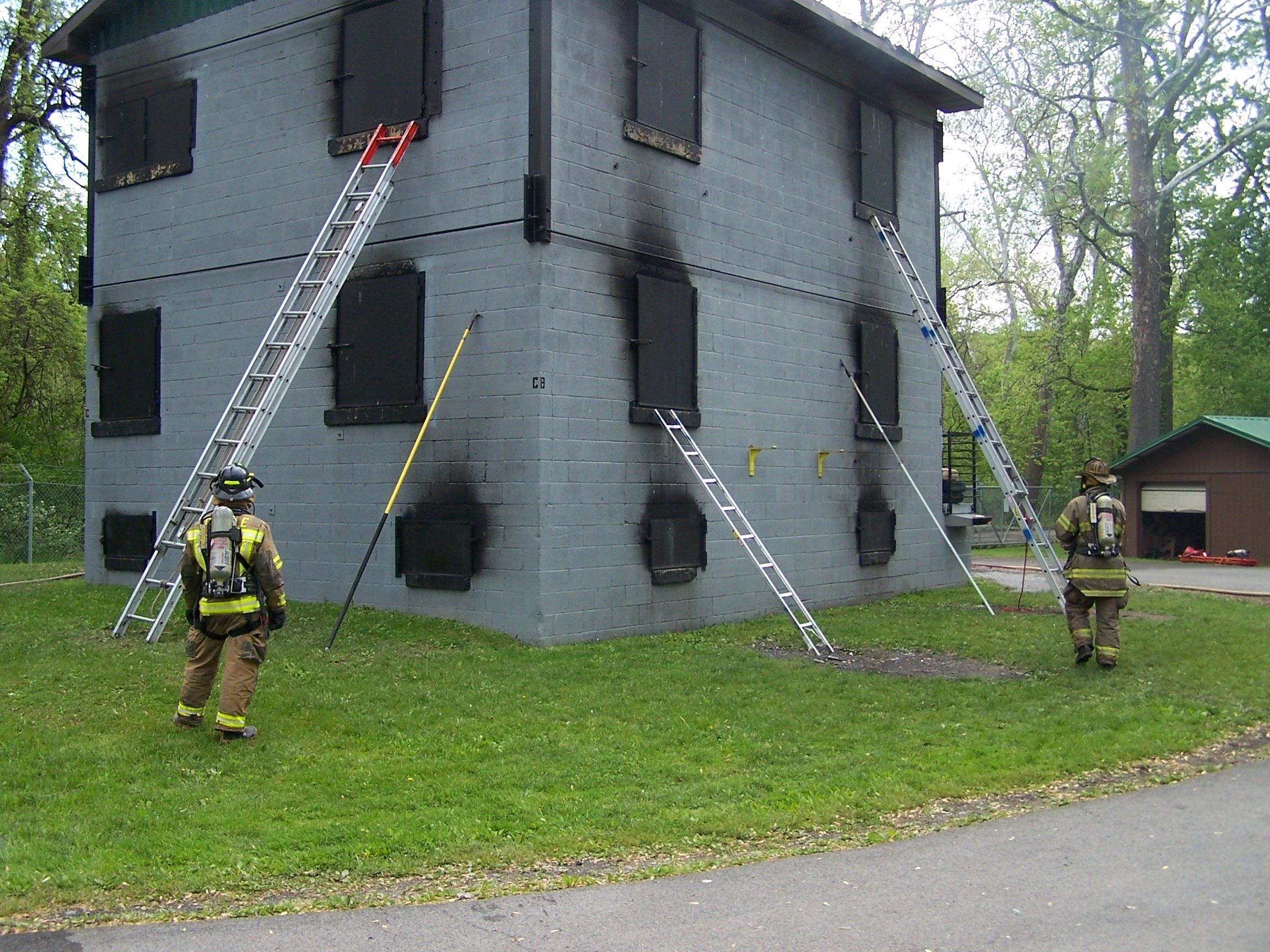 Two firefighters stand in front of a training facility with three ladders rested against it.