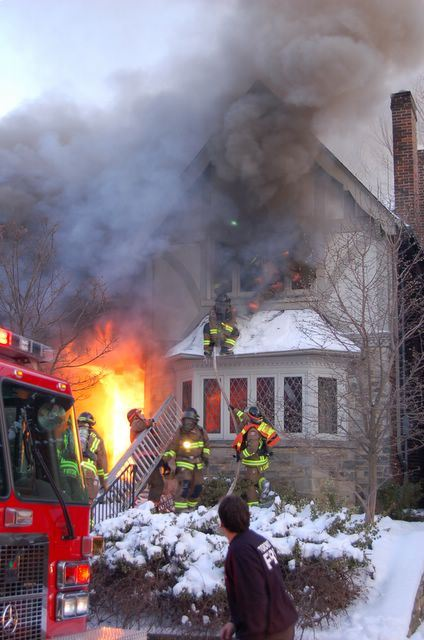 A group of firefighters battle a blazing house fire.
