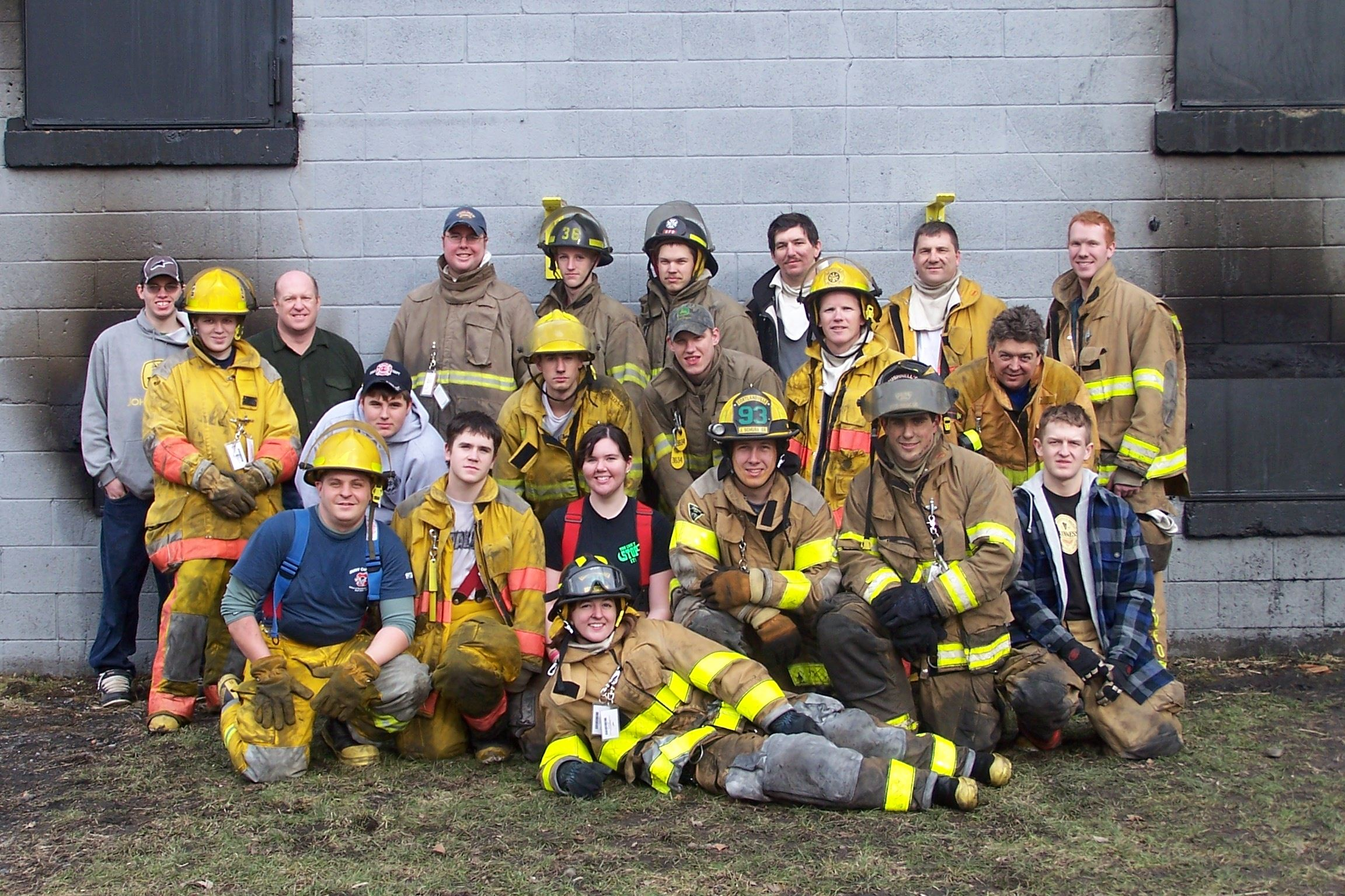 A group of firefighters pose for a picture in front of a building of cement stones.