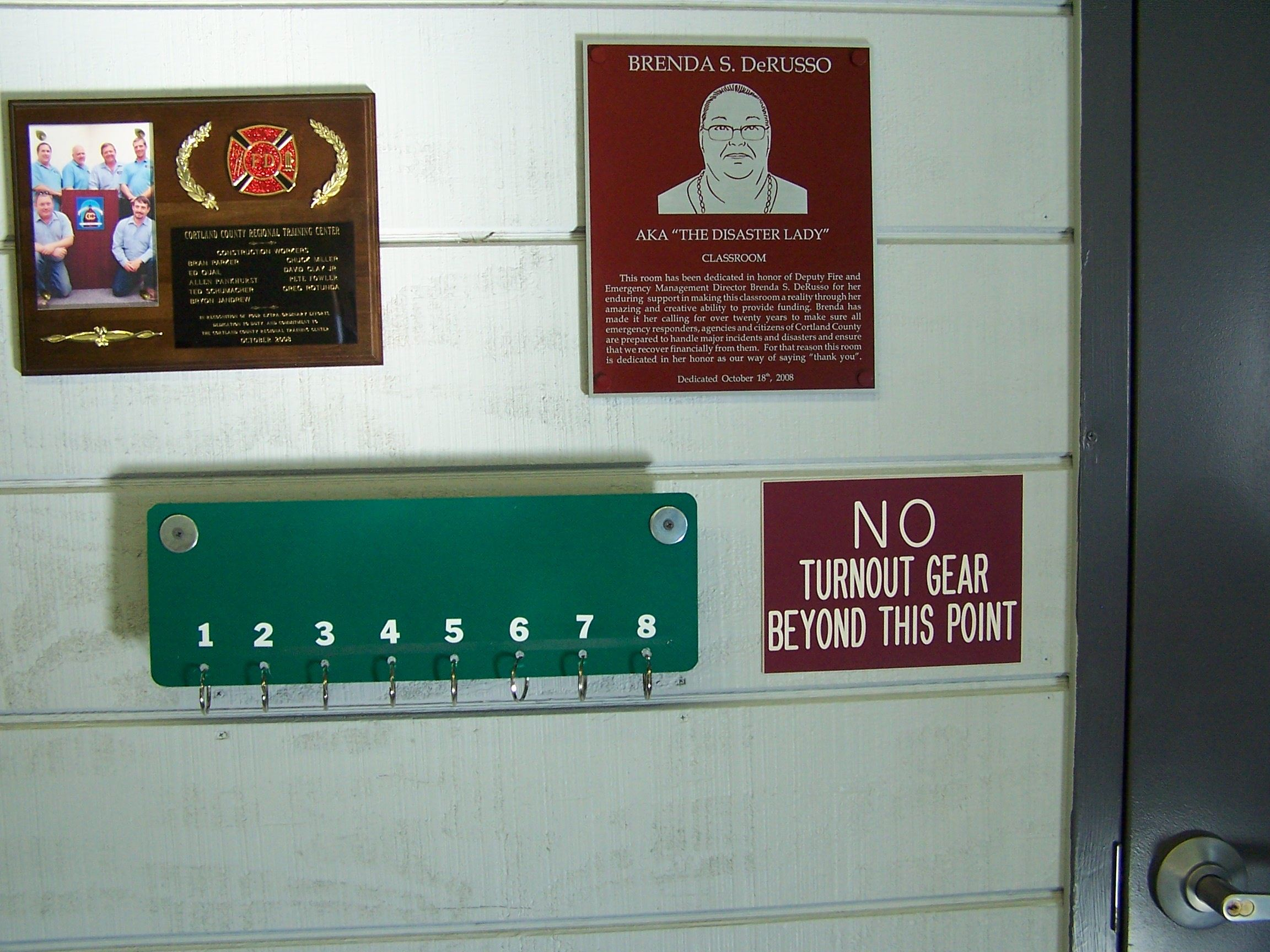 "A wall with a plaque for the training center, a Brenda S DeRusso plaque, a sign with hooks and numbers on it, and a side that reads ""No Turnout Gear Beyond This Point."""