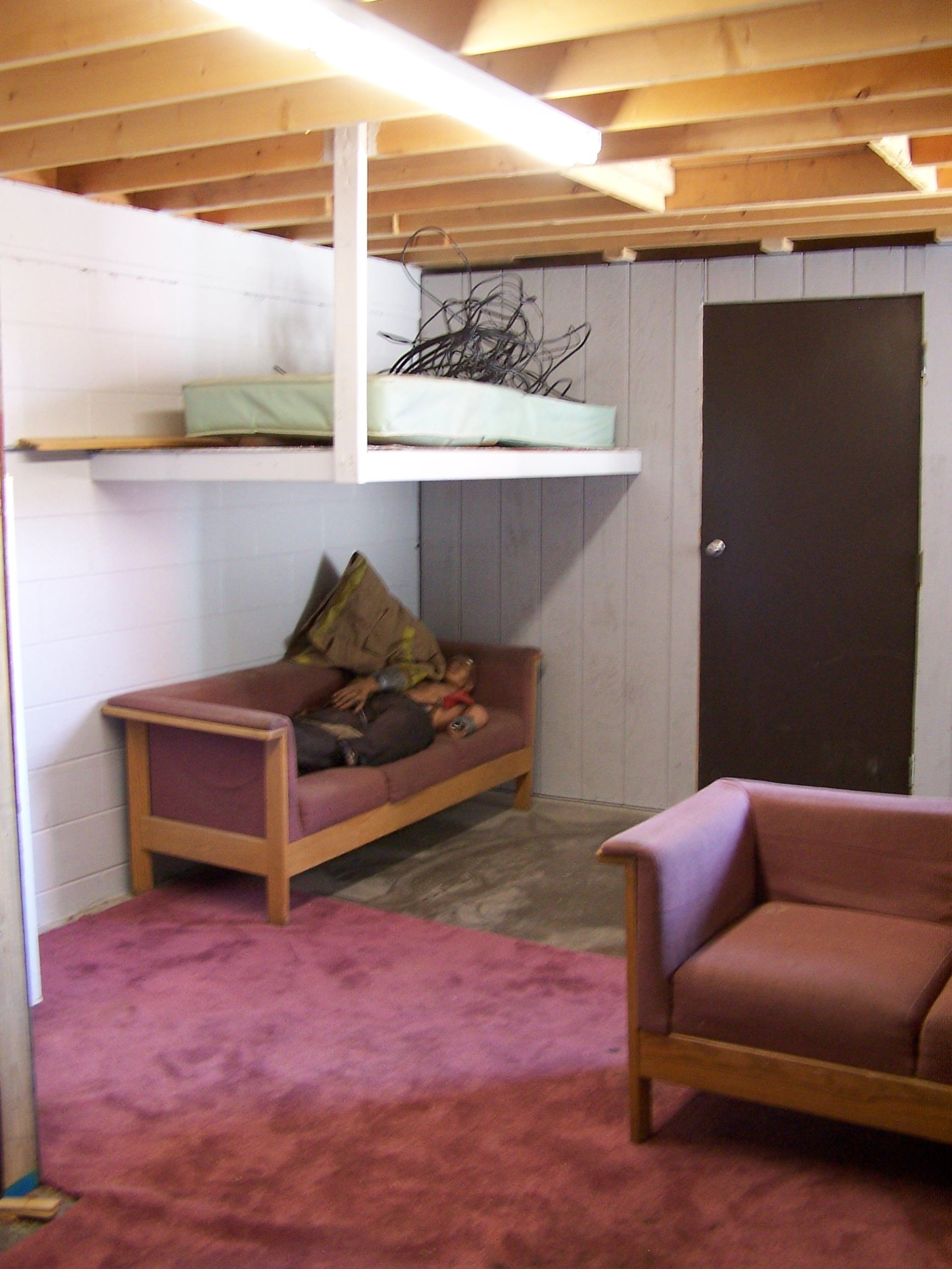 A dorm room mock-up with a couch that has a dummy laying on it and a shelf for a cot.