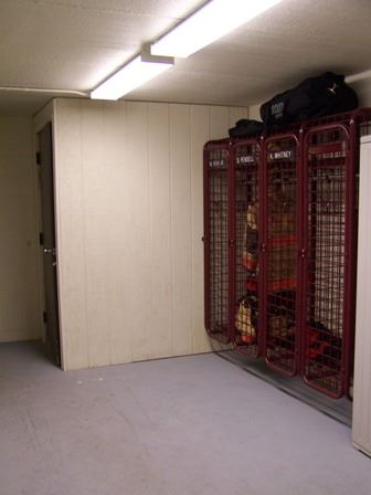 EMS equipment metal storage lockers with a firefighter's suit in one of the lockets and duffle bags on top of the closet.