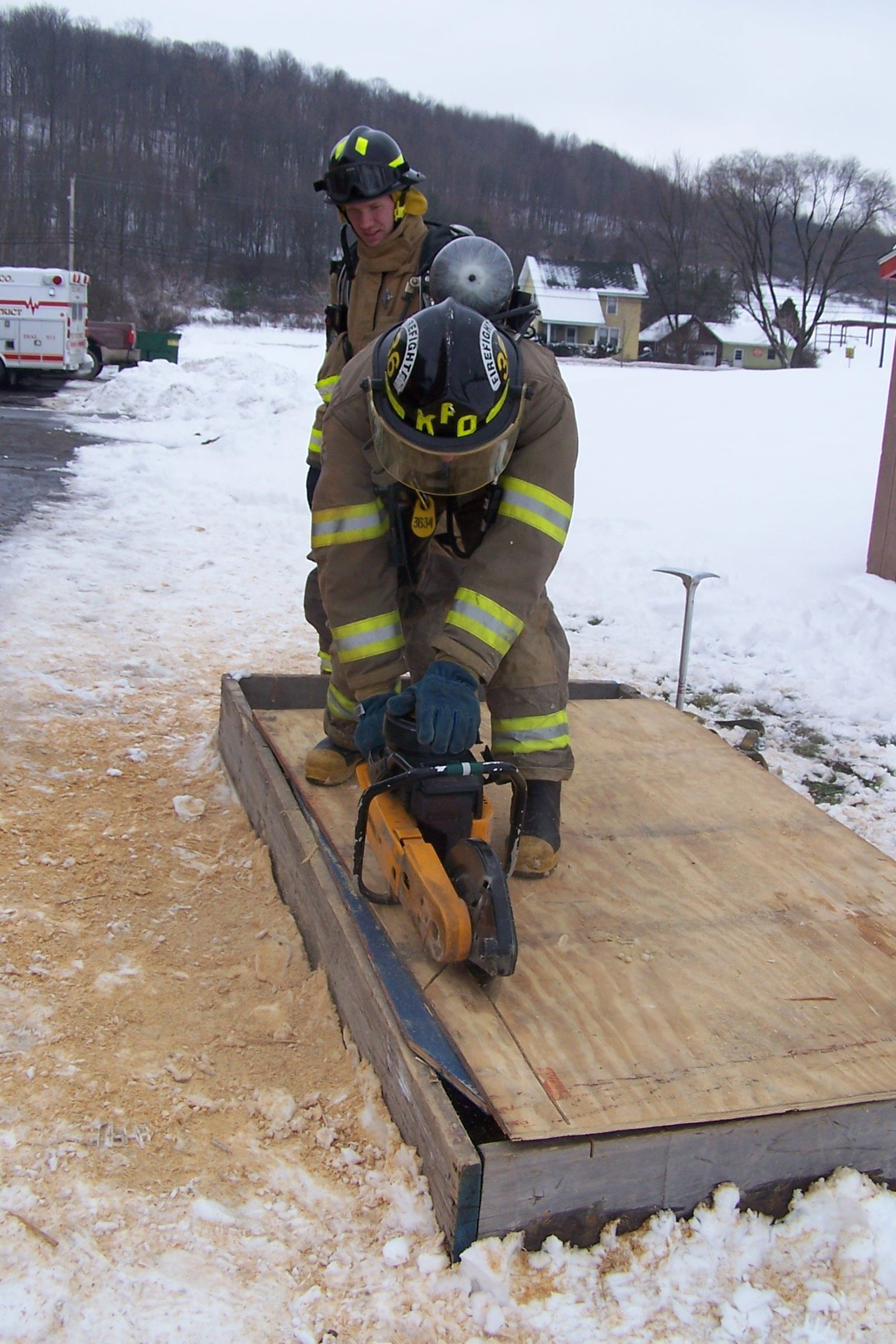 A firefighter practices cutting a wooden roof with a powersaw while another firefighter observes behind him.
