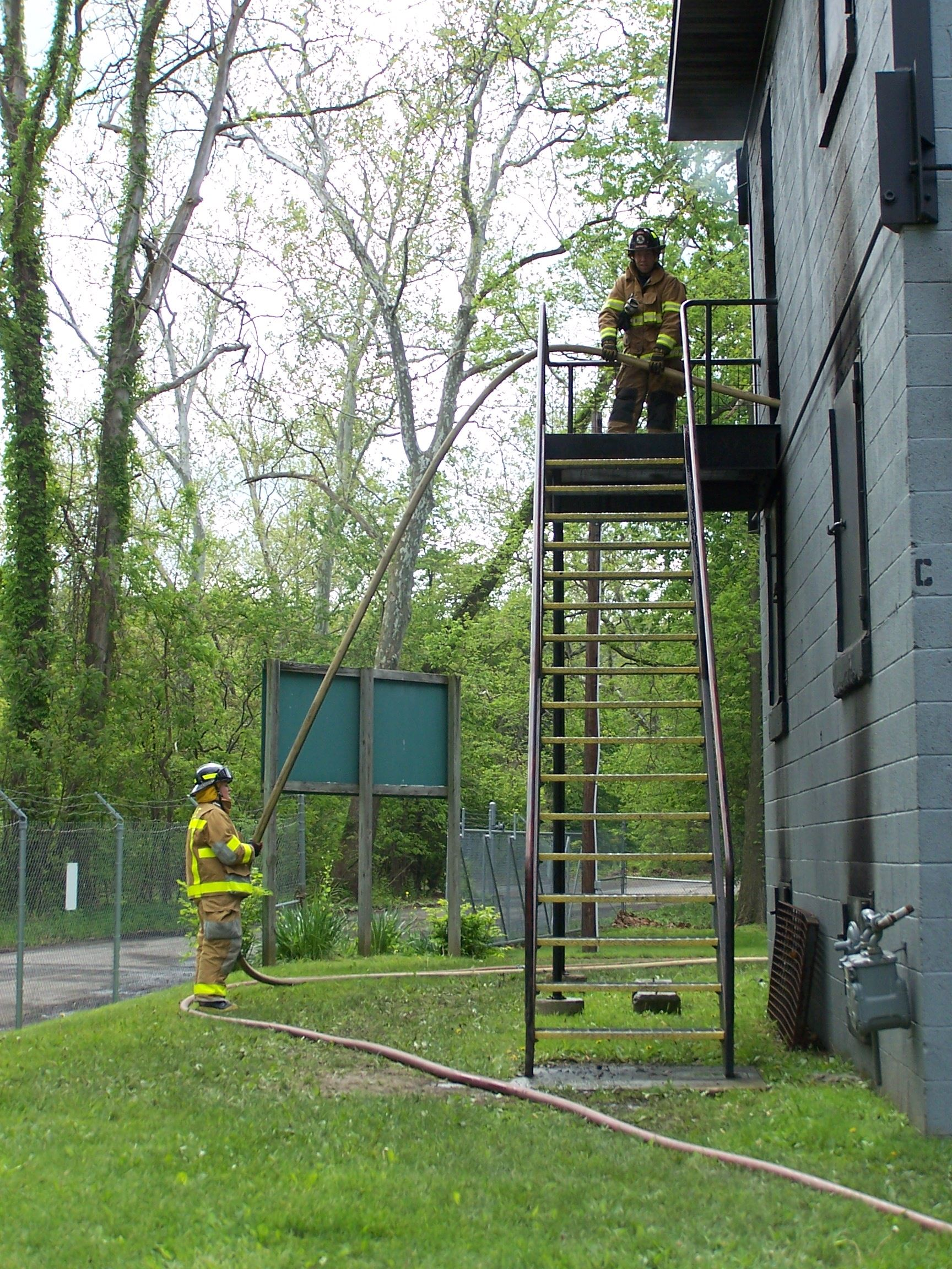Two firefighters on the side of a training facility holding a hose. One firefighter is on the top of a staircase while the other is on the ground.