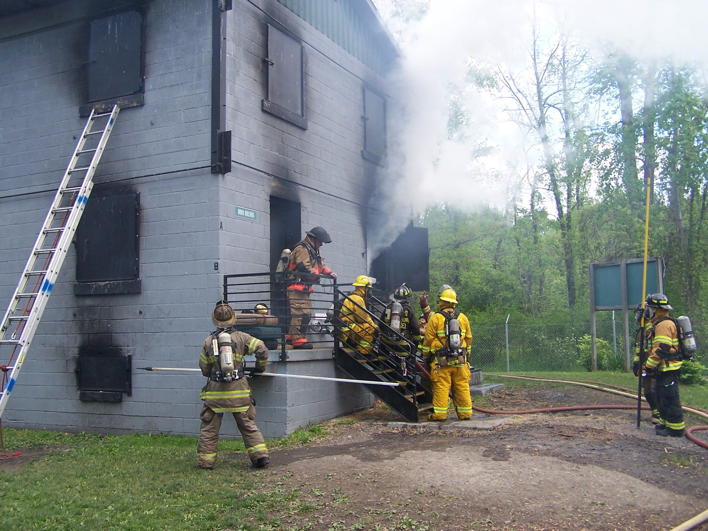 A group of firefighters in front of a smoky training facility. Two of the firefighters are holding poles.