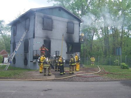 A group of seven firefighters standing in front of a training facility. Two more firefighters are on the side of the facility.