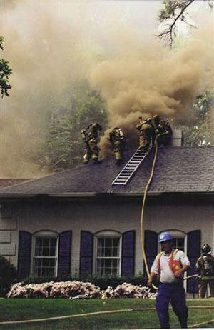 A group of firefighters battle a smoky house fire while standing on the roof.