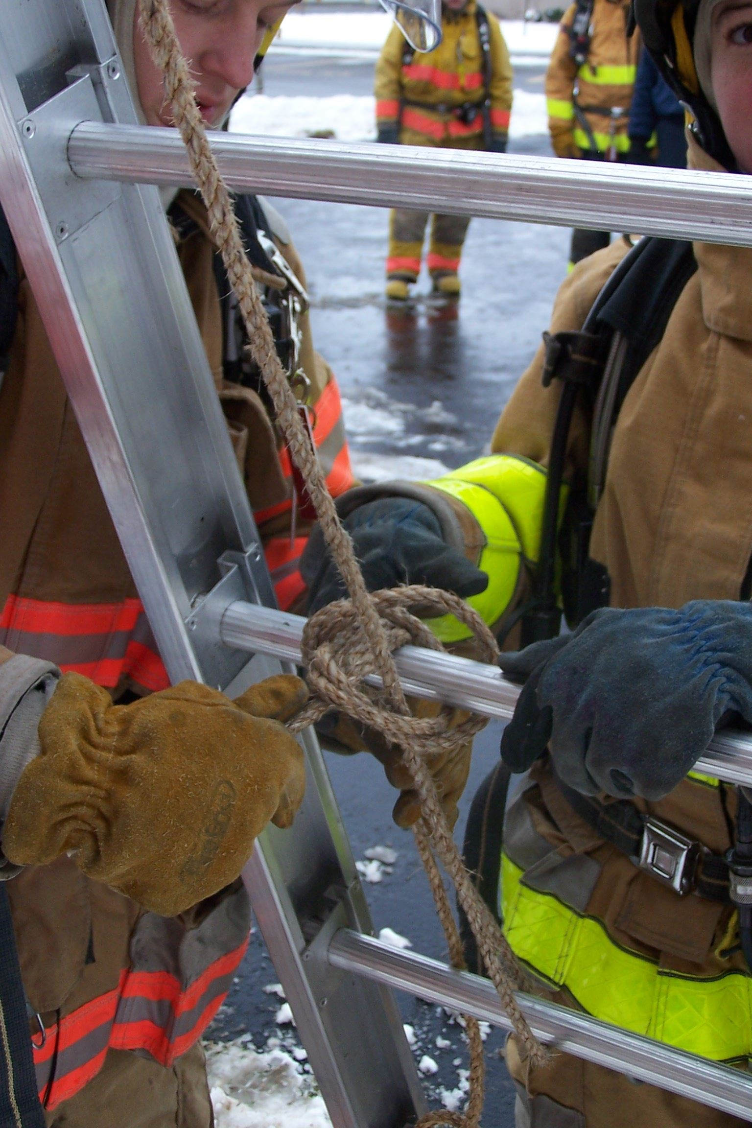 A firefighter ties a knot into a piece of rope around a ladder while another firefighter observes.