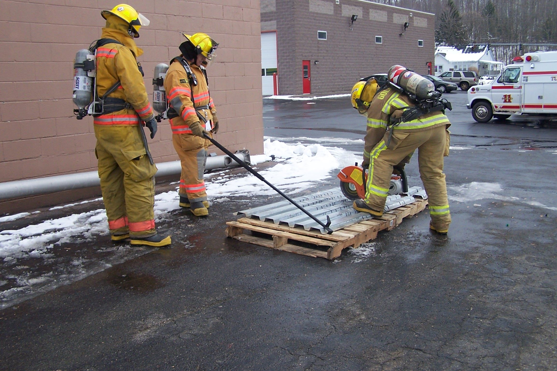 A firefighter demonstrates how to cut a metal roof with a powersaw while two other firefighters observe.